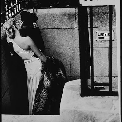 Woman Kissing Gendarme by Helmut Newton
